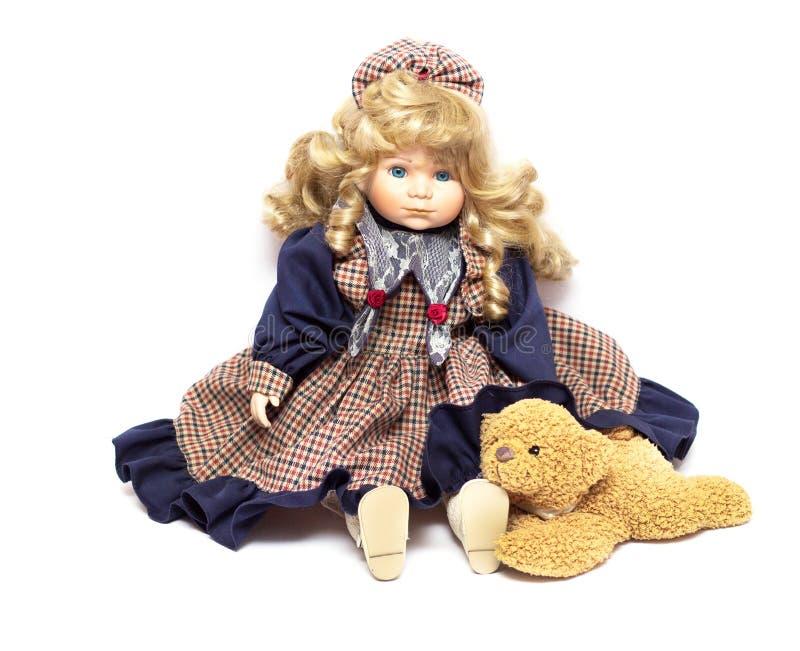 Muñeca vieja de la porcelana en el fondo blanco, muñecas de cerámica y un oso de peluche imagen de archivo