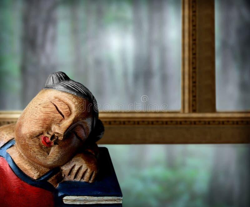 Muñeca y libros en ventana fotografía de archivo