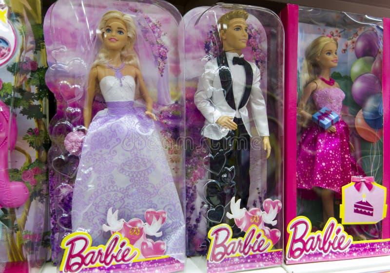 Muñecas de Barbie y de Ken en cajas en estante de la tienda fotos de archivo