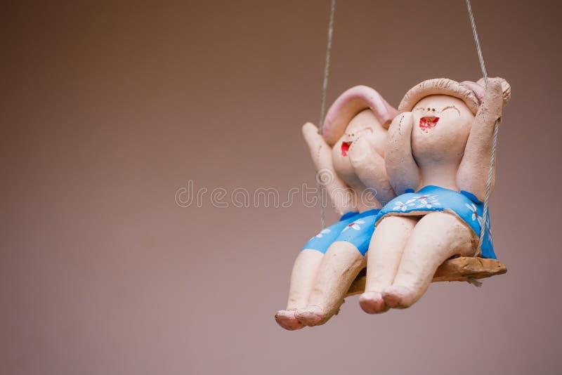 Muñecas del niño de la arcilla que se sientan en oscilaciones en hogar, el concepto de decoración y el arreglo del jardín imagen de archivo