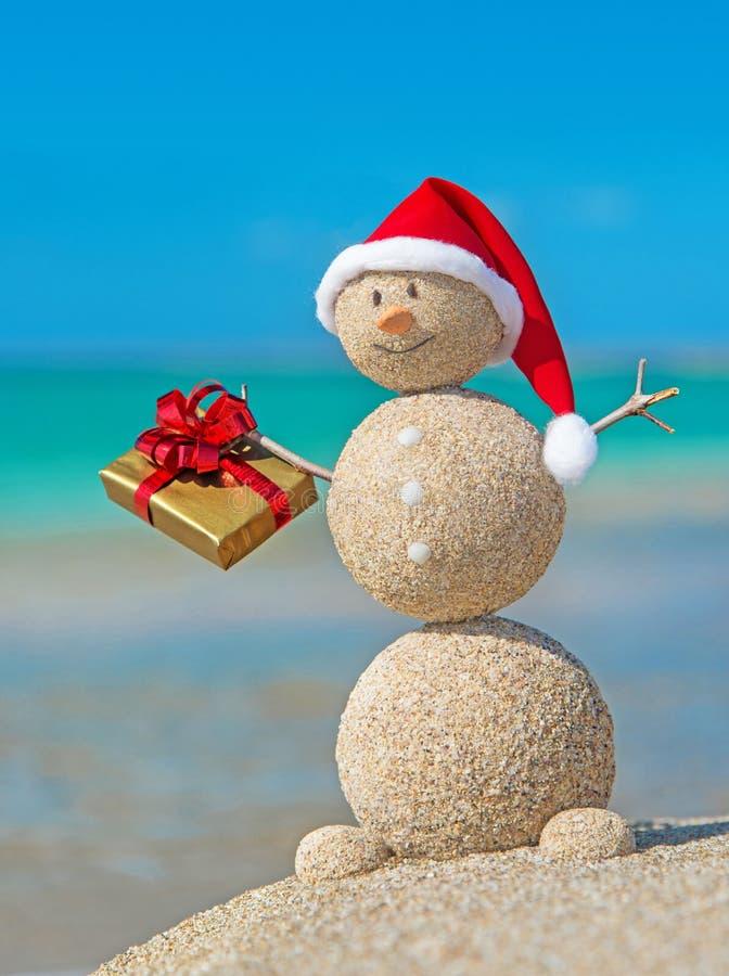 Muñeco de nieve arenoso sonriente en la playa en sombrero de la Navidad con el regalo de oro fotografía de archivo libre de regalías