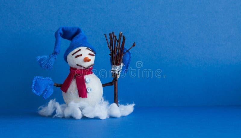Muñeco de nieve cómico en fondo azul Carácter tradicional del muñeco de nieve de las vacaciones de invierno con las manoplas somb imagenes de archivo