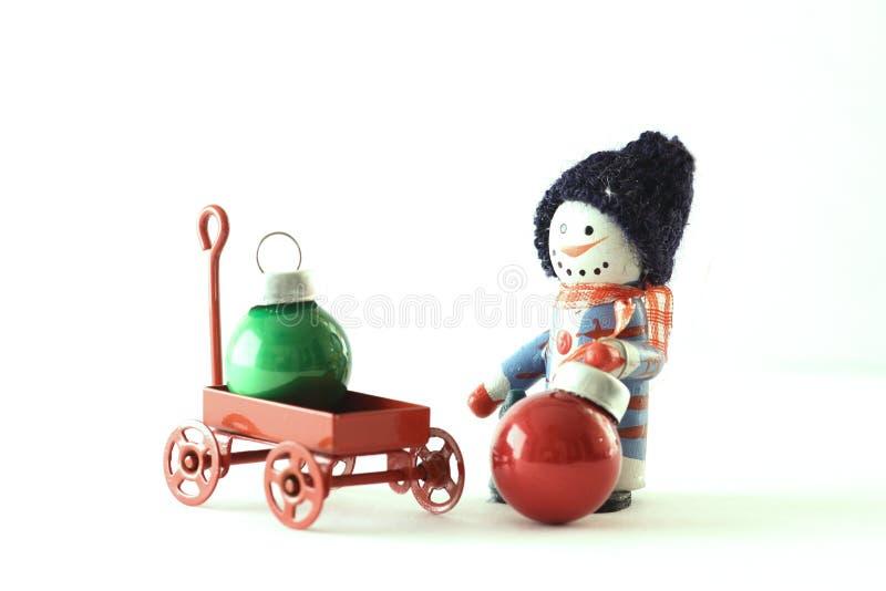 Muñeco de nieve con un carro de las bolas de la Navidad en el fondo blanco imagen de archivo