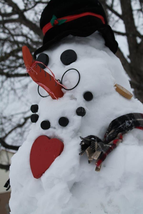 Muñeco de nieve con un corazón grande imagenes de archivo