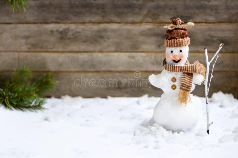 Muñeco de nieve con una escoba en un fondo gris de madera imágenes de archivo libres de regalías