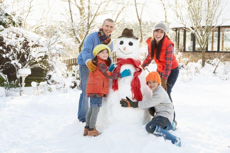 Muñeco de nieve de la fundación de una familia en jardín fotos de archivo libres de regalías