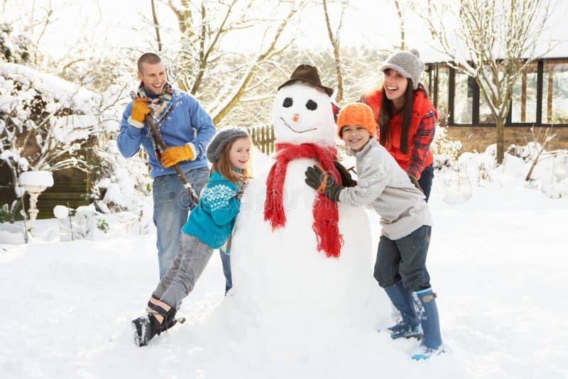 Muñeco de nieve de la fundación de una familia en jardín fotografía de archivo