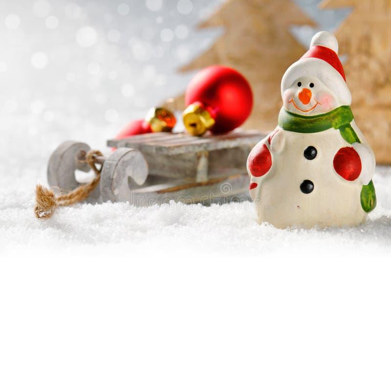 Muñeco de nieve de la Navidad con los presentes en bosque del invierno imágenes de archivo libres de regalías