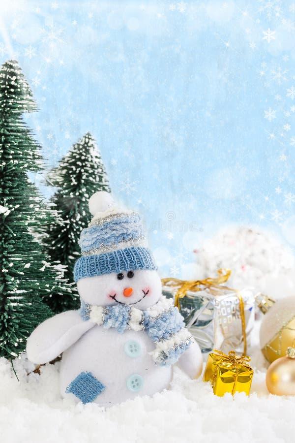 Muñeco de nieve de la Navidad con los regalos en fondo nevoso imagenes de archivo