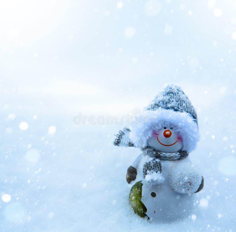 Muñeco de nieve de la Navidad y fondo azul de la nieve imagen de archivo libre de regalías