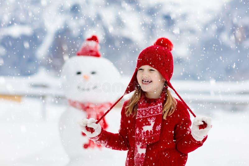 Muñeco de nieve del edificio del niño Los niños construyen al hombre de la nieve imagen de archivo