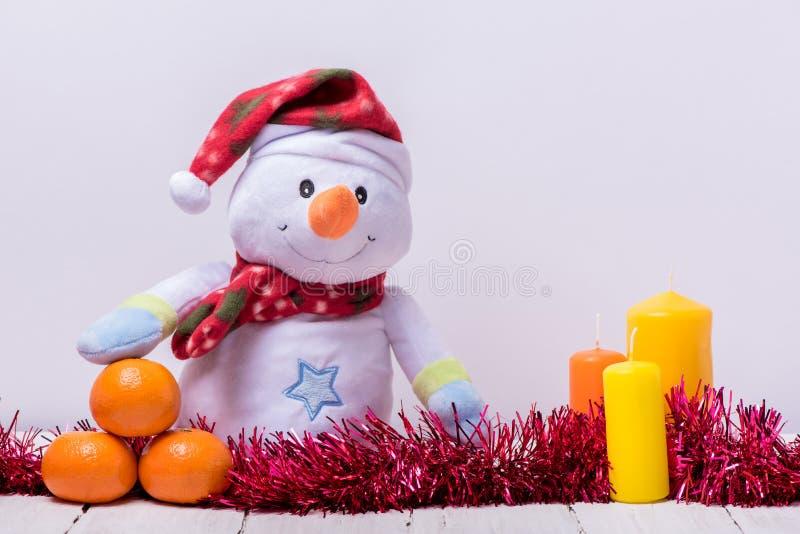 Muñeco de nieve divertido con los mandarines y las velas en un backg de madera blanco fotografía de archivo libre de regalías