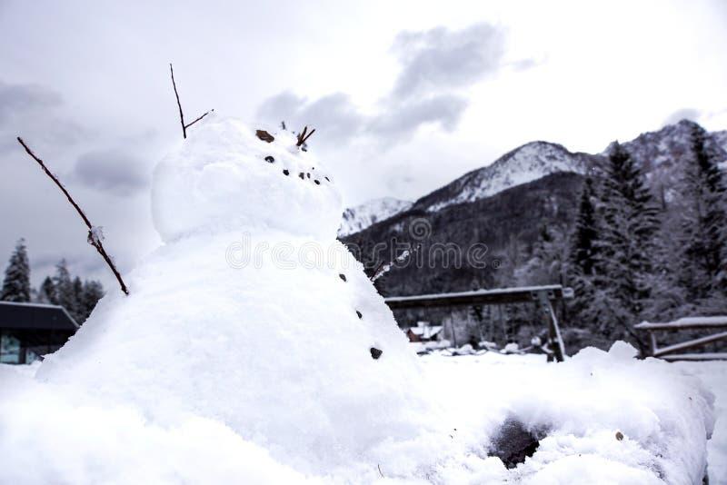 Muñeco de nieve divertido contra las montañas suizas imagenes de archivo