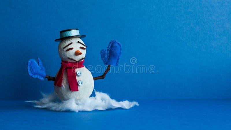 Muñeco de nieve divertido en fondo azul Carácter tradicional del muñeco de nieve del invierno con el sombrero negro de las manopl imagen de archivo libre de regalías