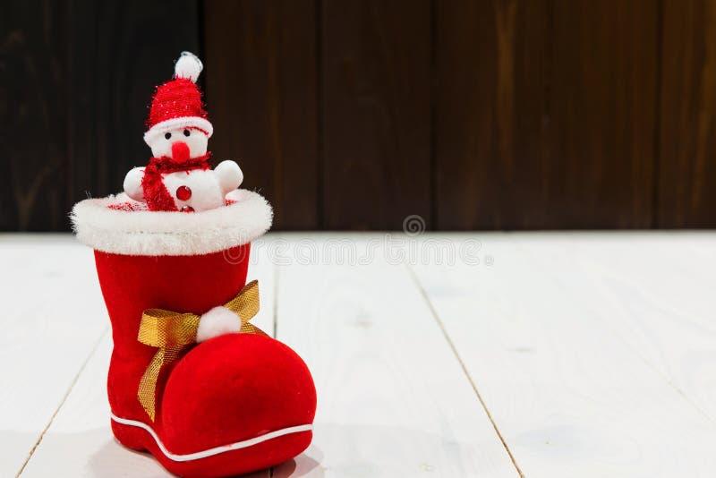 muñeco de nieve en calcetín rojo de Navidad en la madera foto de archivo