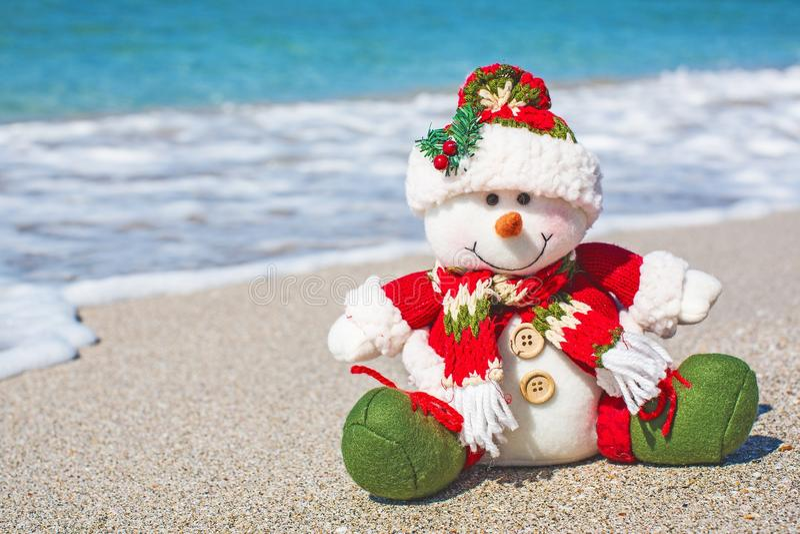 Muñeco de nieve en el sombrero rojo de santa en la playa en sombrero fotografía de archivo libre de regalías