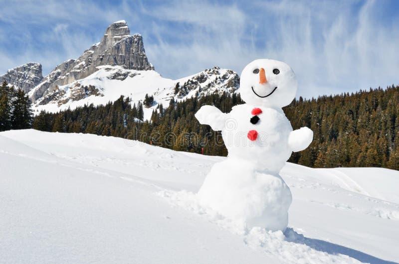 Muñeco de nieve en las montañas imagenes de archivo