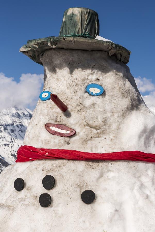 Muñeco de nieve en las montañas austríacas con el sombrero foto de archivo libre de regalías