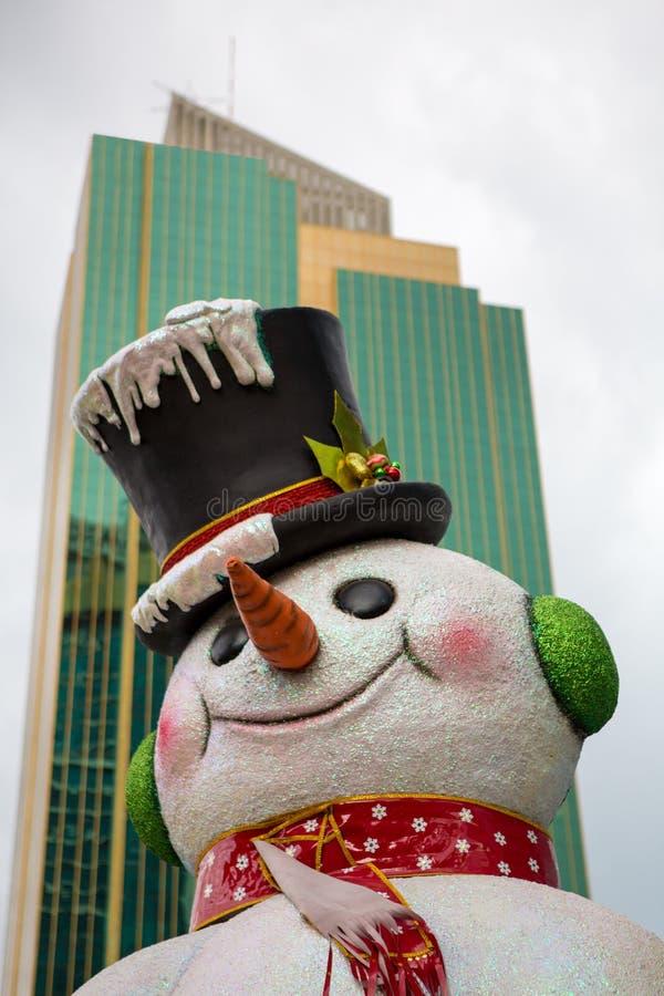 Muñeco de nieve falso de la Navidad con la opinión de la ciudad imagen de archivo libre de regalías