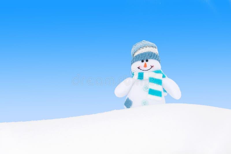 Muñeco de nieve feliz del invierno contra el cielo azul fotografía de archivo libre de regalías