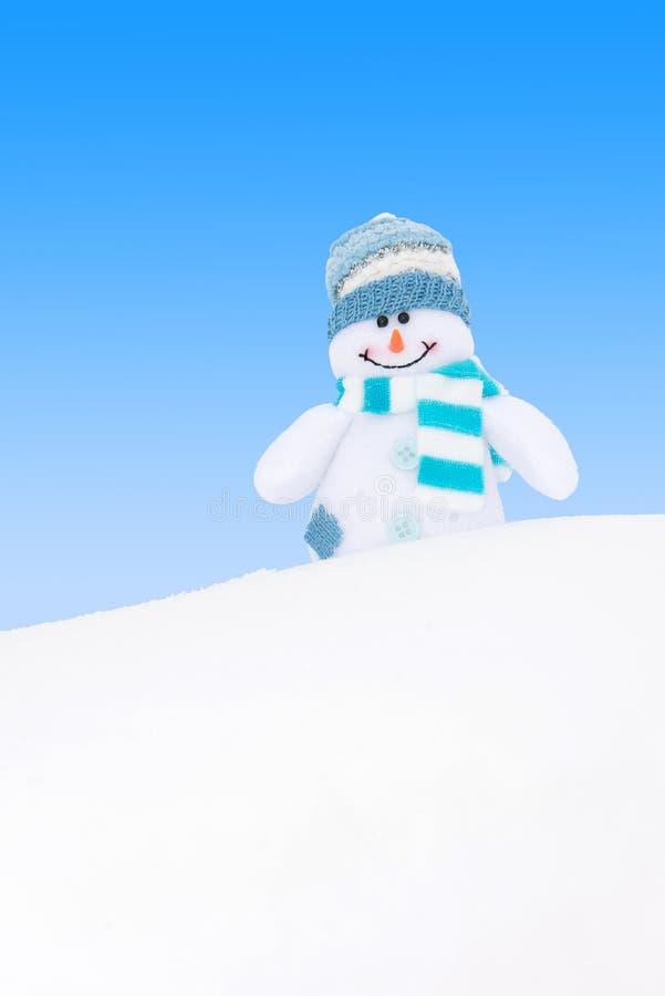 Muñeco de nieve feliz del invierno contra el cielo azul fotos de archivo