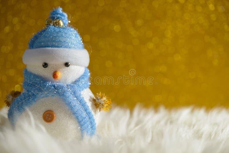 Muñeco de nieve feliz que se coloca en fondo de la nieve de la Navidad del invierno del oro Feliz Navidad y tarjeta de felicitaci imagenes de archivo