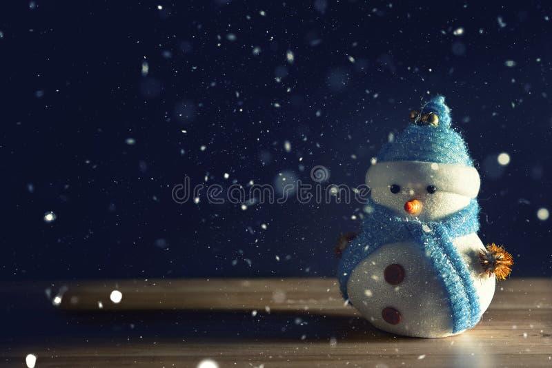 Muñeco de nieve feliz que se coloca en fondo oscuro de la nieve de la Navidad del invierno Feliz Navidad y tarjeta de felicitació fotografía de archivo