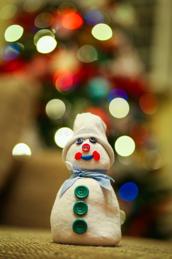 Muñeco de nieve hecho a mano hecho de un calcetín llenado de arroz y adornado con los botones foto de archivo