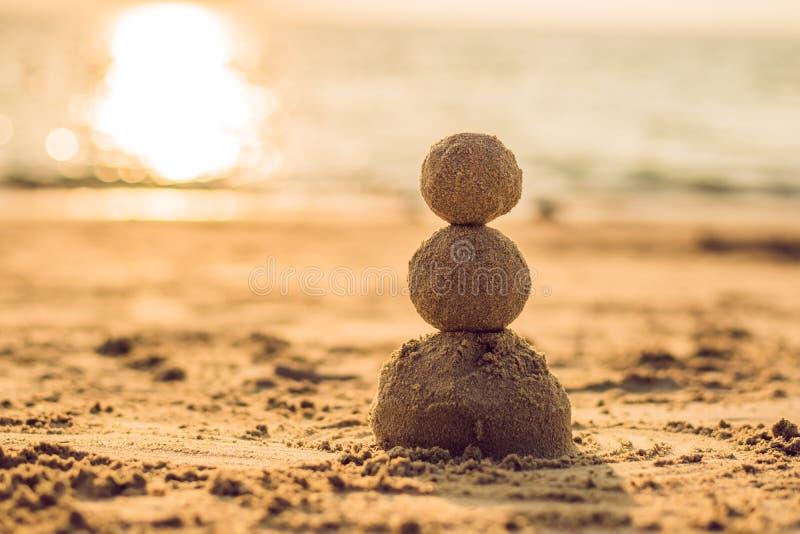 Muñeco de nieve de la Navidad de Sandy en el sombrero y las gafas de sol rojos de santa en la playa soleada Concepto del día de f fotografía de archivo