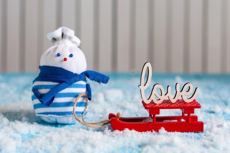 Muñeco de nieve que disfruta de un paseo del trineo con la palabra AMOR imagen de archivo libre de regalías