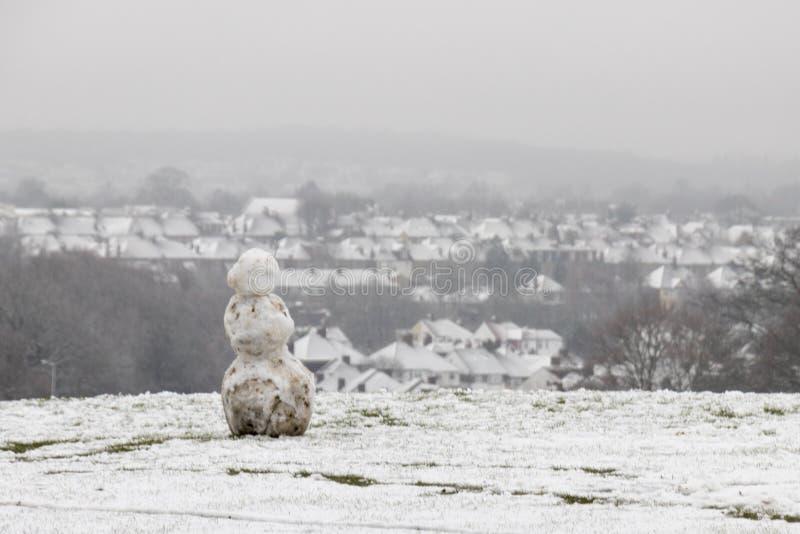 Muñeco de nieve que mira casas nevadas fotos de archivo libres de regalías