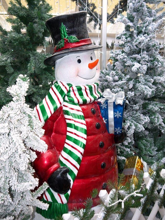 Muñeco de nieve sonriente con la caja y el sombrero de copa de regalo imagenes de archivo
