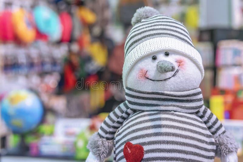 Muñeco de nieve sonriente del juguete suave en un sombrero y un suéter rayados imagenes de archivo