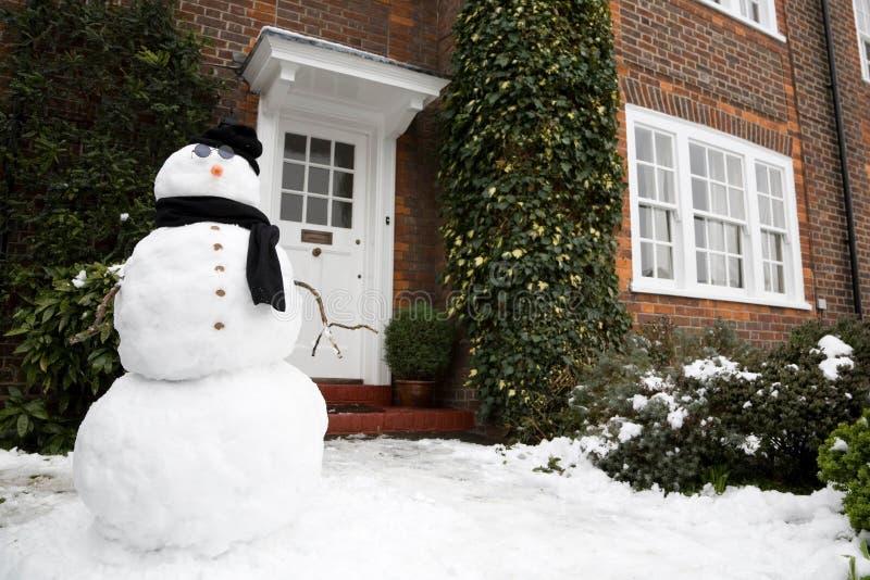 Muñeco de nieve y casa fotografía de archivo libre de regalías