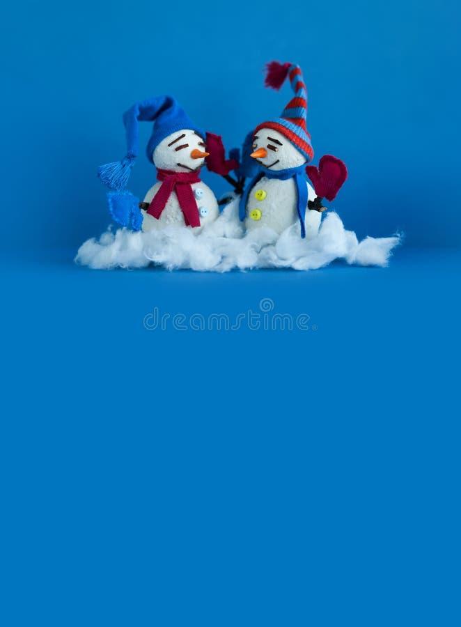 Muñecos de nieve felices en fondo azul Caracteres tradicionales del muñeco de nieve del invierno con las manoplas de la bufanda y imagenes de archivo