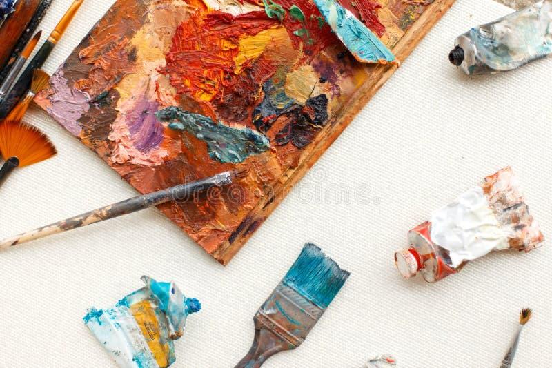 Muśnięć narzędzia dla artysty z nafcianą farbą kłamają na kanwie zdjęcie royalty free