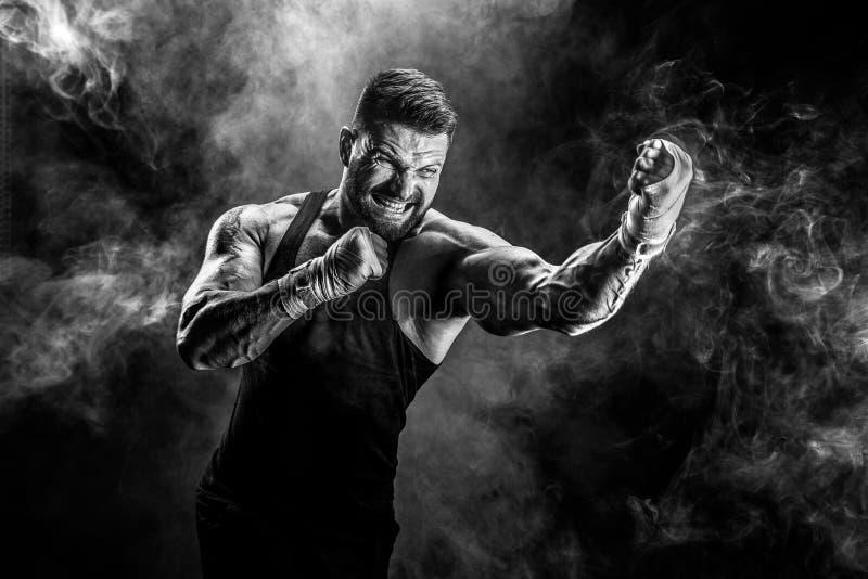 Muay ταϊλανδική πάλη μπόξερ αθλητικών τύπων στο μαύρο υπόβαθρο με τον καπνό στοκ φωτογραφίες