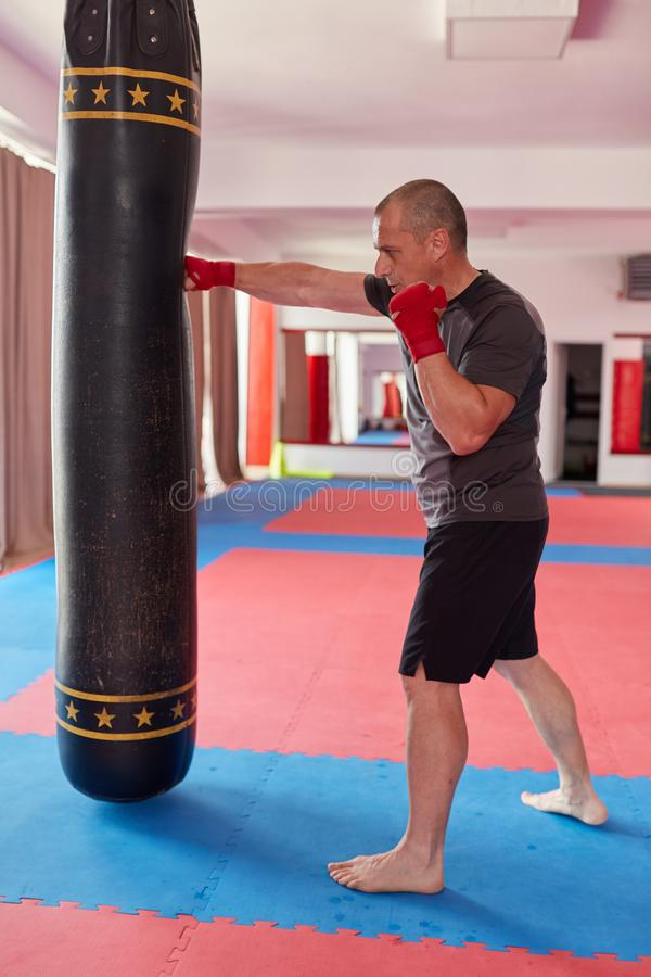 Muay thai fighter with heavy bag. Muay thai fighter with hands wrapped training with heavy bag stock photos