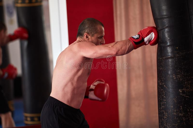 Muay thai fighter working with heavy bag. Muay thai fighter hitting the heavy bag in the gym royalty free stock photo