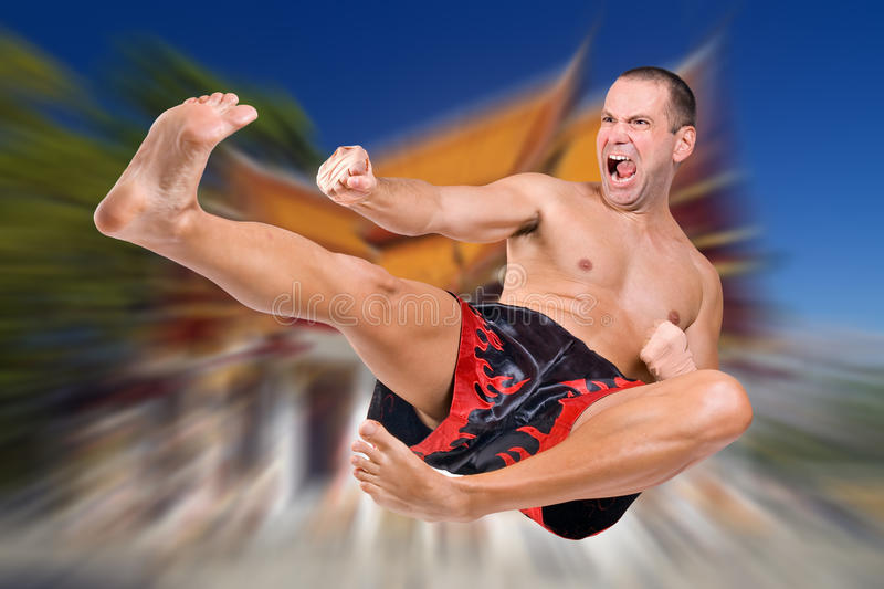 Muay Thai fighter. Jumping on background of Buddhist monastery royalty free stock photography