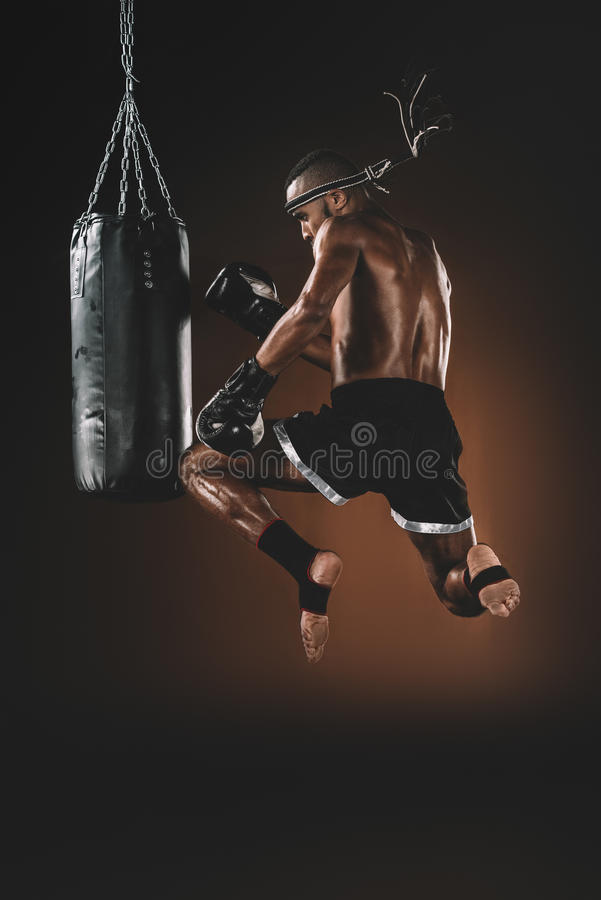 Muay thai fighter training with punching bag, action sport concept stock image