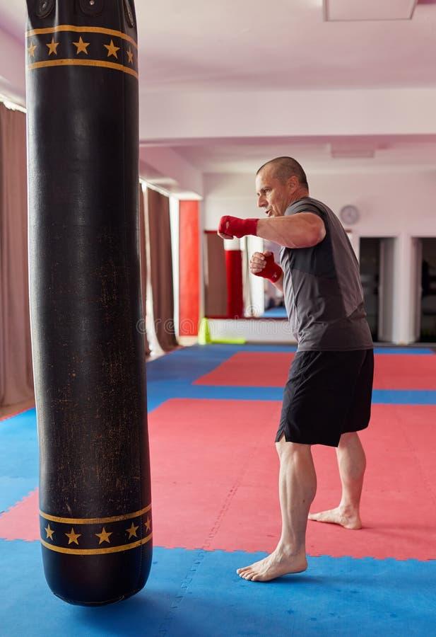 Muay Thaise vechter met zware zak stock fotografie