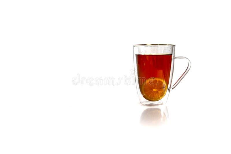 Mucca di tè nero caldo con limone isolato su fondo bianco immagine stock