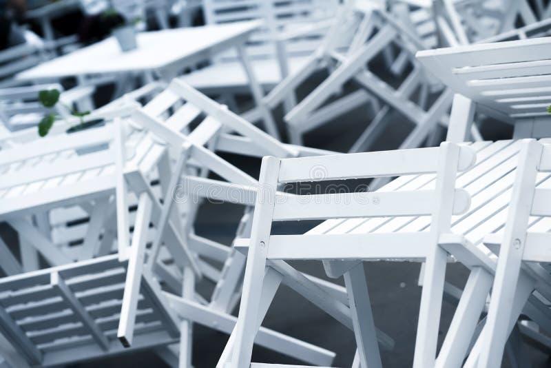 Mucchi delle sedie di plastica bianche invertite sulle tavole in ristorante chiuso sul primo piano del terrazzo Bello caos grafic fotografia stock