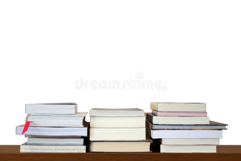 Mucchi o pila di libri per la lettura e lo studio sullo scaffale di legno sul fondo bianco della parete in bianco immagini stock libere da diritti