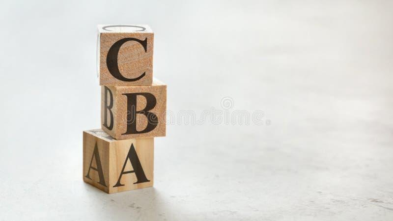 Mucchio con tre cubi di legno - lettere CBA che significano valutazione dei costi e dei redditi loro, spazio per più testo/immagi fotografia stock