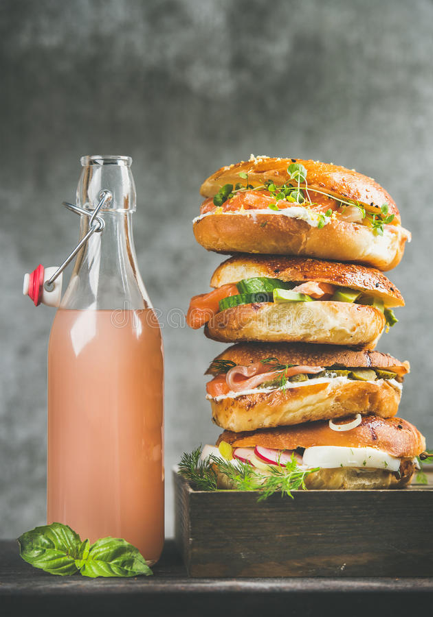Mucchio dei bagel con il salmone, uova, verdure, capperi, crema-formaggio, limonata fotografie stock