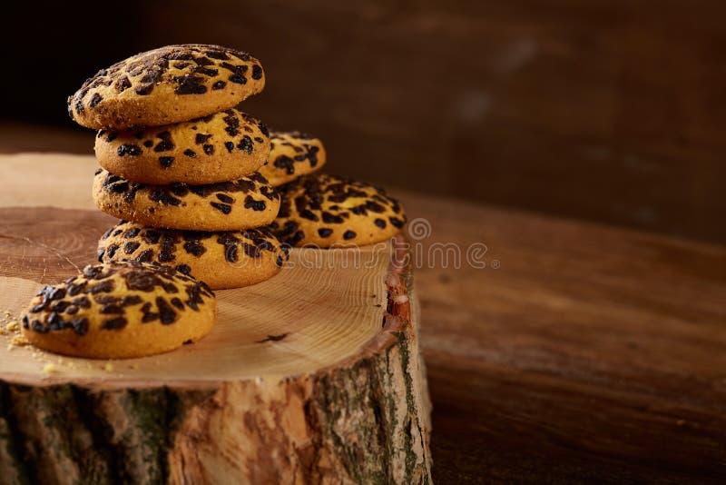 Mucchio dei biscotti su un ceppo di legno rotondo sopra fondo di legno rustico, primo piano, fuoco selettivo fotografia stock