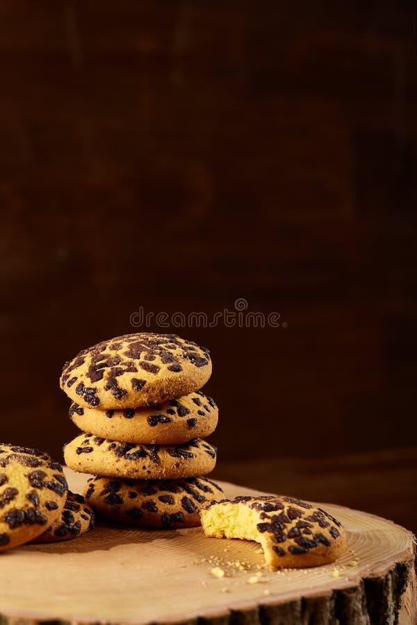Mucchio dei biscotti su un ceppo di legno rotondo sopra fondo di legno rustico, primo piano, fuoco selettivo fotografie stock