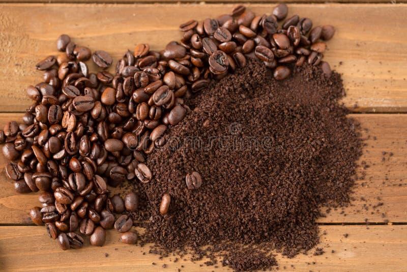 Mucchio dei chicchi e dei motivi di caffè nel mezzo di legno immagine stock
